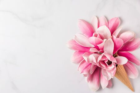 Creative layout made with pink magnolia flowers in ice cream cone on white marble background. Flat lay. top view. wedding or womans day composition. spring concept Stok Fotoğraf