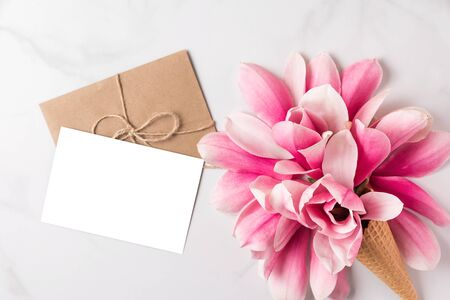 Blank white greeting card with spring pink magnolia flowers in waffle cone on white background. mock up. flat lay. top view. holiday festive background
