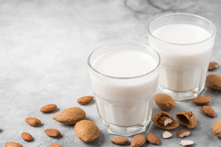 Plant based almond vegan milk in glasses with nuts on concrete background. Dairy free milk. close up