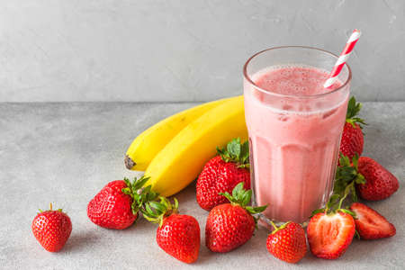 Glass of healthy smoothie or milkshake made of strawberry, banana and almond milk with a straw. Raw, vegan, vegetarian drink concept