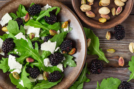 Fresh salad with arugula, feta cheese, blackberries and pistachios in a plate on rustic wooden background. top view