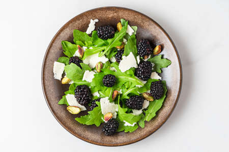Fresh salad with arugula, goat cheese, blackberries and pistachios in a plate on white background. top view. healthy diet food Imagens
