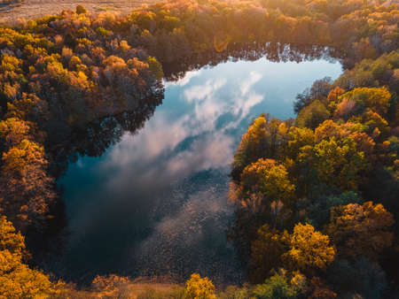 Aerial view of lake in beautiful autumn forest. Beautiful landscape with trees with green, red and orange leaves. Top view from flying drone