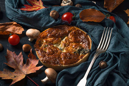 Chicken, mushroom and tomatoes pie quiche with autumn leaves on dark fabric on black background with fork. Still life