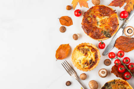 Autumn food. Chicken, mushroom, spinach and tomatoes pies quiche with autumn leaves and cutlery on white marble table. top view. Flat lay