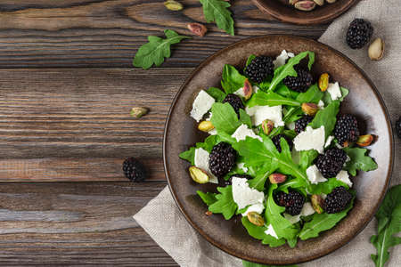 Healthy vegetarian salad with arugula, goat cheese, blackberries and pistachios on rustic wooden table. top view with copy space Banco de Imagens
