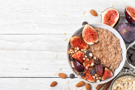 Bowl of oatmeal porridge with figs, cinnamon, chocolate and almonds on white wooden background. top view with copy space. diet breakfast. healthy food Imagens