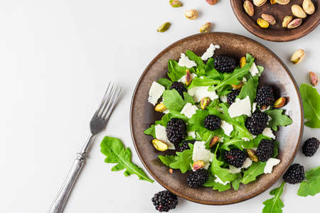 Healthy vegetarian salad with arugula, feta cheese, blackberries and pistachios on white marble table with fork. top view with copy space. diet menu