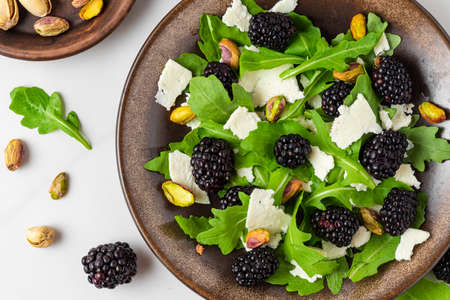 Fresh salad with arugula, goat cheese, blackberries and pistachios in a plate on white background. top view. healthy diet food Banco de Imagens