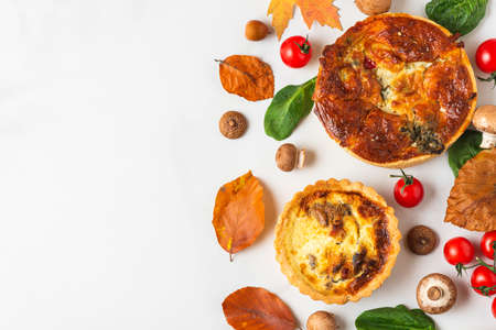 Chicken, mushroom, spinach and tomatoes pies quiche with autumn leaves on white marble table. top view. Flat lay Banco de Imagens
