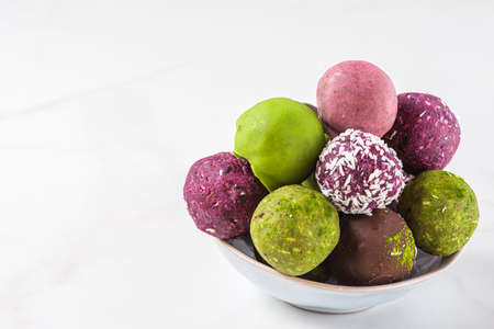 Raw handmade energy balls, healthy vegan dessert on a white background. close up with copy space Imagens