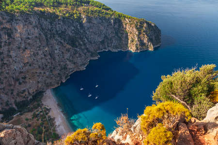 Aerial view of Butterfly Valley with yachts in the city of Oludeniz or Fethiye, Mugla, Turkey in the sunny morning