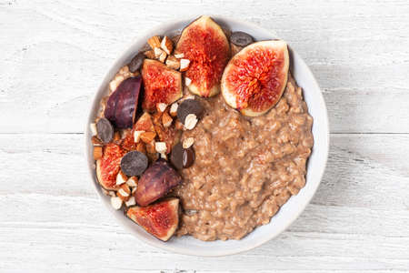 Oatmeal porridge with figs, cinnamon, chocolate and nuts in a bowl on white wooden background. top view. diet breakfast. healthy food Imagens