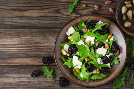 Fresh salad with arugula, feta cheese, blackberries and pistachios in a plate on rustic wooden background with copy space. top view Imagens