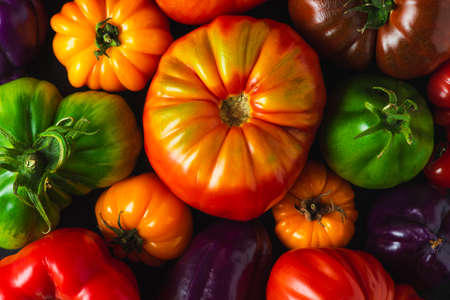 Colorful organic tomatoes and pepper composition on black background. top view. flat lay. Vegan diet food cooking concept