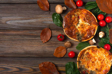 Chicken, mushroom, spinach and tomatoes pies quiche with autumn leaves on rustic wooden background. top view. Flat lay