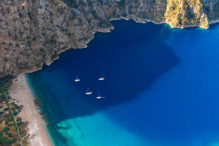 The Butterfly Valley (kelebekler vadisi) with sandy beach and yachts in the city of Oludeniz or Fethiye, Mugla, Turkey in the sunny morning Imagens