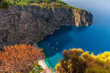 Aerial view of Butterfly Valley with sandy beach, azure water and yachts in the city of Oludeniz or Fethiye, Mugla, Turkey in the sunny morning