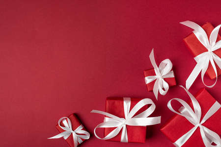 Red gifts with white ribbon, present on red background. top view. Happy Holidays. Valentine's day. Birthday. Merry Christmas and Happy New Year