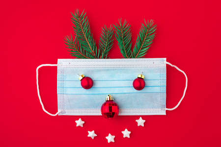 Festive coronavirus christmas concept made from face mask, fir tree and decorations on red background. flat lay. top view