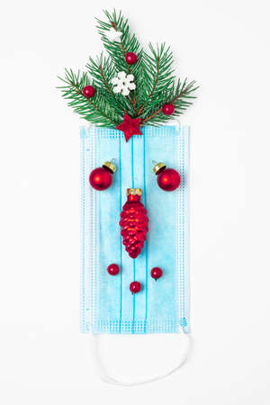 Coronavirus christmas concept made from face mask, fir tree and decorations on white background. flat lay. top view. vertical orientation