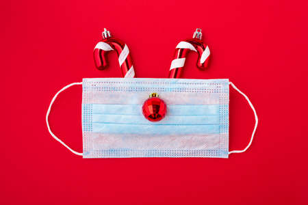 Festive coronavirus christmas concept made from face mask and decorations on red background. flat lay. top view