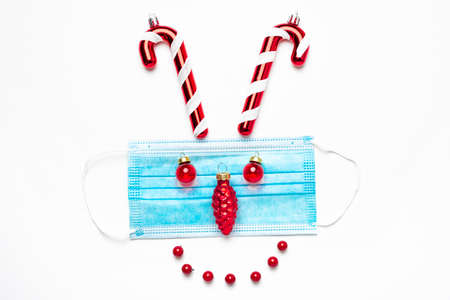 Festive coronavirus christmas concept made from face mask and decorations on white background. flat lay. top view