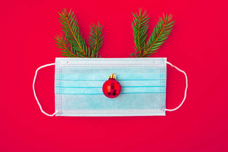 Festive coronavirus christmas concept made from face mask, fir tree and red decoration on red background. flat lay. top view Imagens