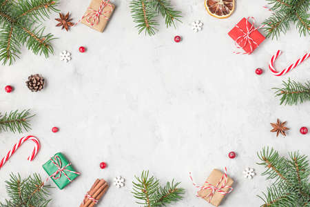 Christmas frame made of fir branches, festive decorations, gift boxes and pine cones on concrete background. Flat lay. top view with copy space