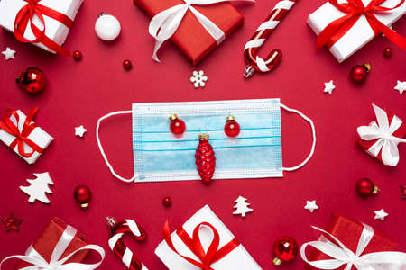 Coronavirus Christmas concept. Face mask in frame made of Christmas gift boxes and decorations on red background. flat lay