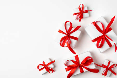 White gifts with red ribbon, present on white background. top view. Happy Holidays. Valentine's day. Birthday. Merry Christmas and Happy New Year
