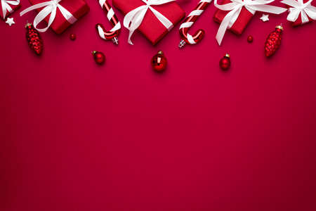 Christmas or Happy New Year composition made of red gift boxes and holiday decorations on red background. flat lay. top view with copy space Banco de Imagens