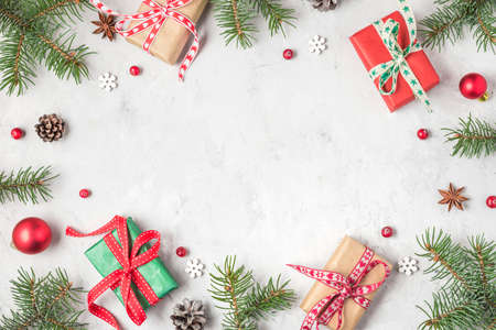 Christmas frame made of fir branches, red berries, gift boxes and pine cones on concrete table. Christmas background. Flat lay. top view with copy space Banco de Imagens