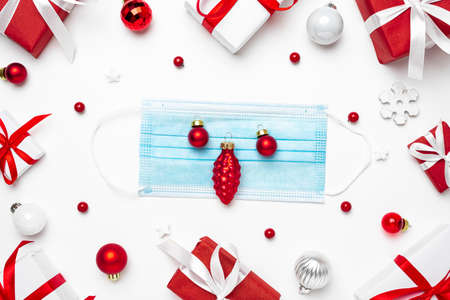 Coronavirus Christmas concept. Face mask in frame made of Christmas gift boxes and decorations on white background. flat lay