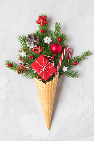 Christmas decorations, fir tree, snowflakes, gift box and candy in waffle ice cream cone. Minimal Christmas concept. Flat lay. Vertical orientation