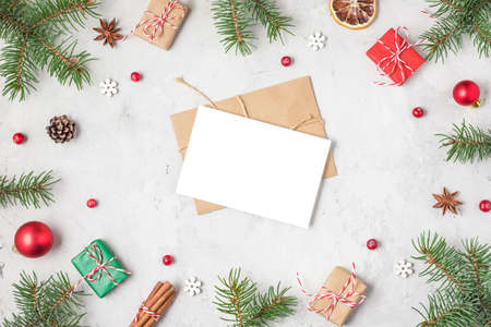 Christmas or Happy New Year greeting card in frame made of fir tree branches, holiday decorations and gift boxes on concrete background. flat lay. top view with copy space Banco de Imagens