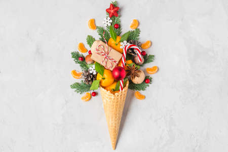 Ice cream cone with Christmas decorations. Fir tree, mandarin, candy, nuts and gift box. Minimal Christmas concept. Flat lay. top view
