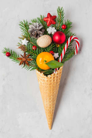 Christmas fir tree branches with Christmas food and decorations in waffle ice cream cone. Winter holiday concept. flat lay. vertical orientation Imagens