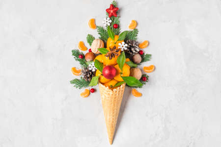 Christmas decorations in waffle ice cream cone with fir branches, tangerine fruits and decorations on concrete background. top view. flat lay