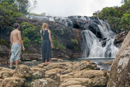 foreigners: HORTON PLAINS, SRI LANKA  MAY 23 2015: A group of young foreigners are watching the waterfall at the end of Bakers Falls in Horton plains, Sri Lanka on 23rd May 2015