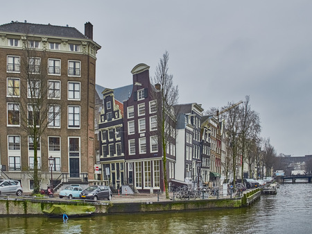 Amsterdam cityscape in January with canals and leaning old houses with gray winter sky Banco de Imagens