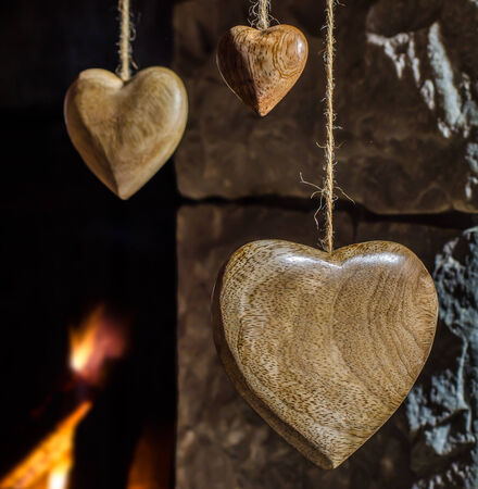 stone  fireplace: Wooden hearts hanging against an old stone fireplace