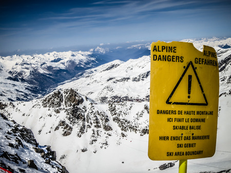 Dangerous - yellow board with warning on the top of the mountain, Val Thorens, France photo