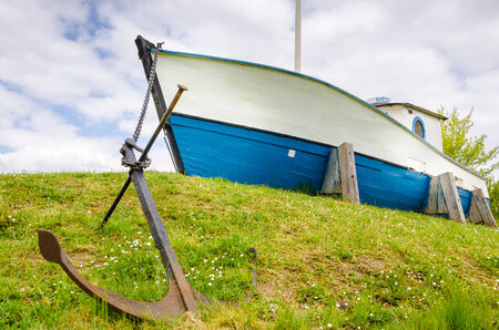Anchored boat laying in the grass field resembling waves photo
