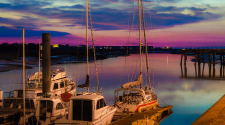 Sail boats docked on marine in beautiful sunset sky, horizontal photo taken at evening just after sunset photo