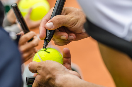 the autograph: Tennis player signs autograph on a tennis ball after win, closeup photo showing tennis ball and hands of a man making signature  Stock Photo
