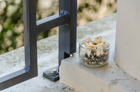 Cigarette butts in ashtray on a balcony  Smoking inside not allowed  photo
