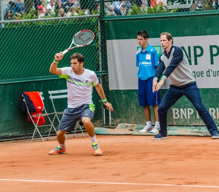 an umpire: Paris, France  May 29, 2014  Dusan Lajovic of Serbia plays forhand return while the umpire shows that the ball was in, during the 2nd round match at French Open, Roland Garros on May 29, 2014 in Paris, France  Editorial