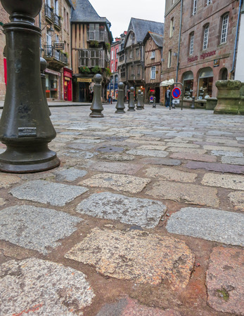 Old tiles on pavement and short poles in old French city, low angle view on old center of Dinan, France Banque d'images