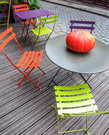Pumpkin on round table on wooden patio